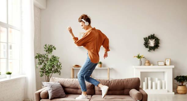 mulher alegre ouvindo música e dançando em sofá macio em casa no dia de folga - dançar - fotografias e filmes do acervo