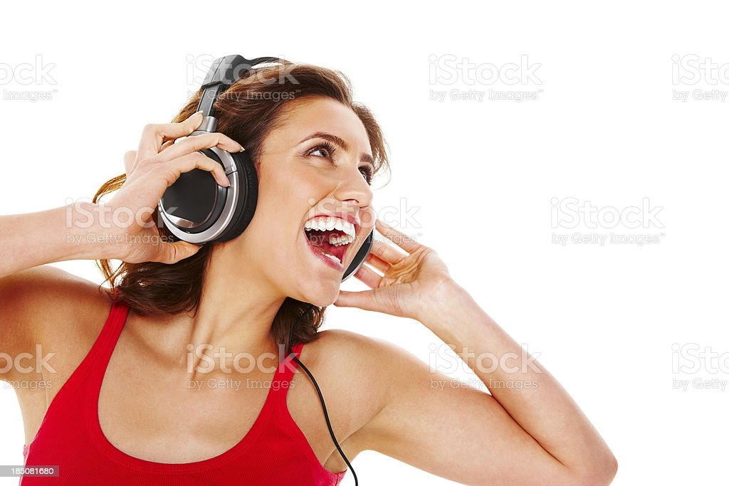 Cheerful woman listening to music on headphones against white royalty-free stock photo