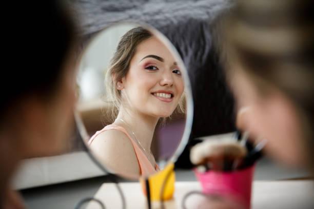 Fröhliche Frau schaut in den Spiegel – Foto