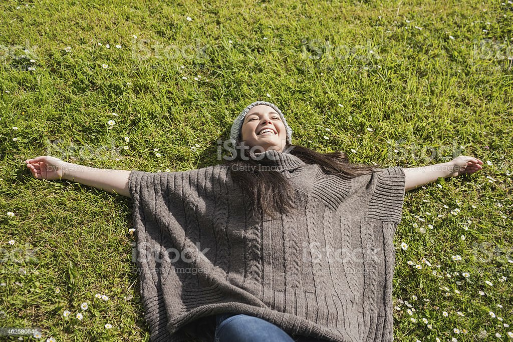 Cheerful woman lying on the grass in green meadow royalty-free stock photo