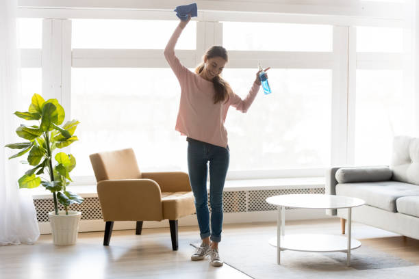 Cheerful woman makes house cleaning holding rag spray bottle detergent Full-length woman in casual clothes dance do house cleaning holds blue rag spray bottle detergent feels happy, qualified housekeeping specialist agency hiring, quick fast and easy home chores concept cleaning equipment stock pictures, royalty-free photos & images