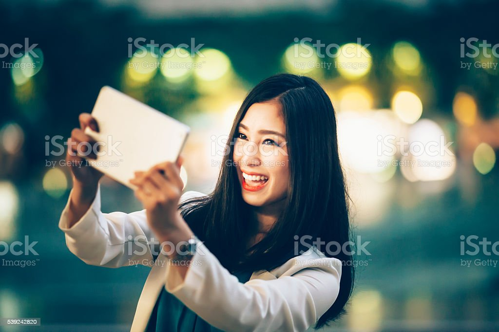 Cheerful woman making selfie with digital tablet on street royalty-free stock photo