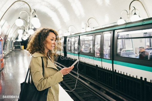 Cheerful woman listening to music from her smartphone while waiting for the train to go home, subway train on background.
