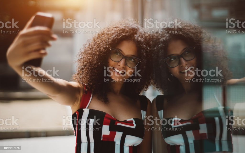 Cheerful woman photographing herself using cellphone stock photo