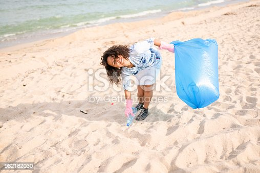 962184460 istock photo Cheerful woman picking up garbage during local clean up 962182030