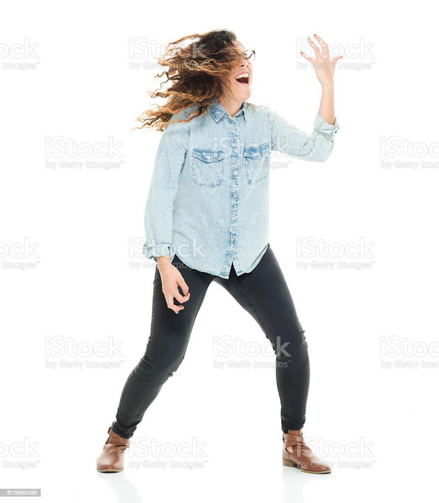 Cheerful woman playing air guitar stock photo