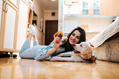 Cheerful woman playing with her dog in apartment.