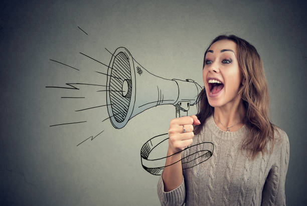 Cheerful woman sharing with news using loudspeaker Content young woman screaming in loudspeaker making announcement. communication stock pictures, royalty-free photos & images