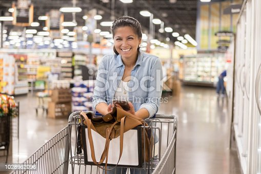 istock Cheerful woman shops for groceries 1028962096