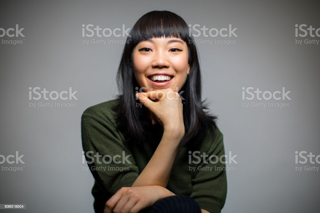 Cheerful woman sitting against gray background stock photo