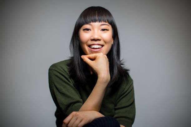 cheerful woman sitting against gray background - mano sul mento foto e immagini stock