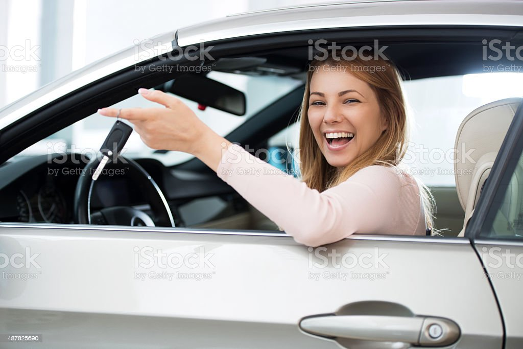 Cheerful woman sitting in a car holding new car keys. stock photo