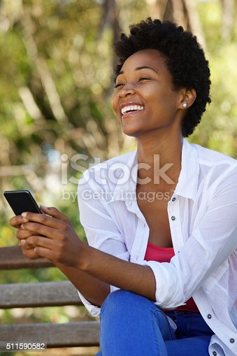 istock Cheerful woman sitting on a bench with a mobile phone 511590582