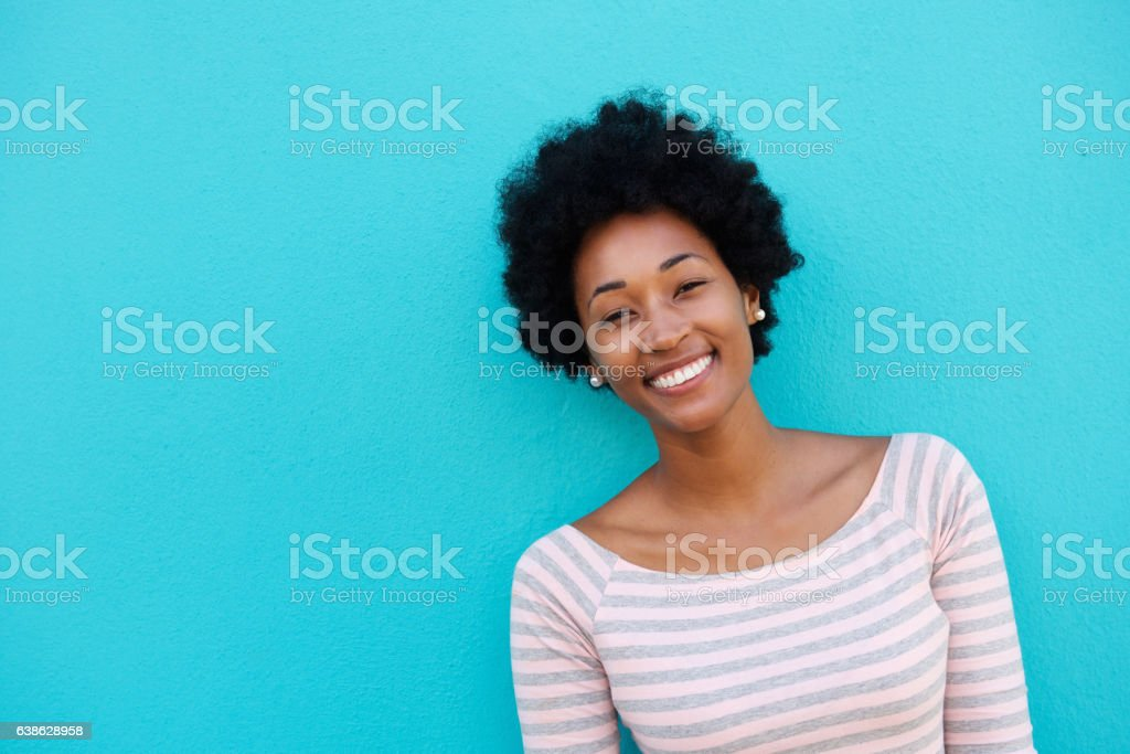 Cheerful woman standing against blue wall stock photo