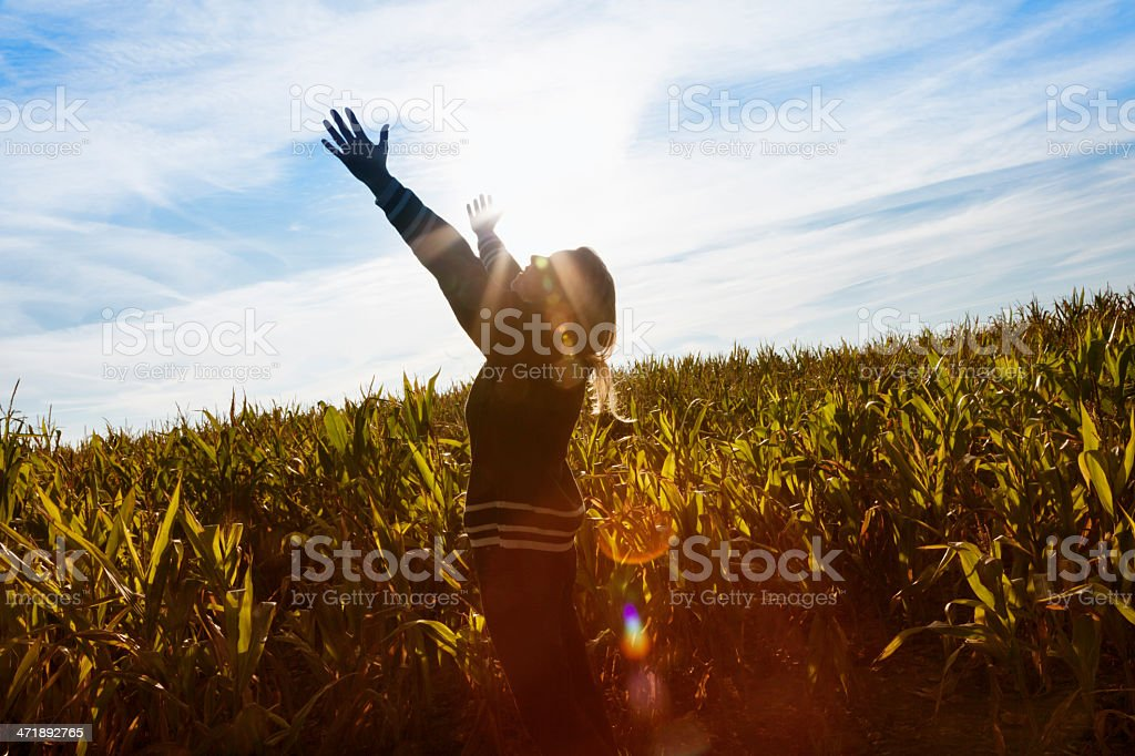 cheerful woman standing in field arms raised freedom stock photo
