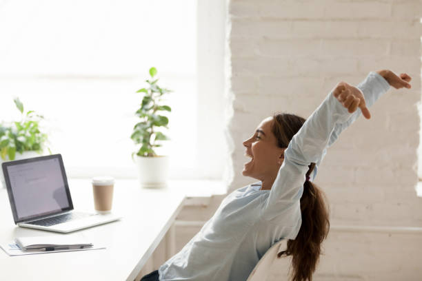 cheerful woman stretching raising hands up sitting at workplace - incentivo foto e immagini stock