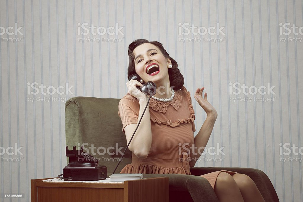 Cheerful woman talking on landline phone stock photo