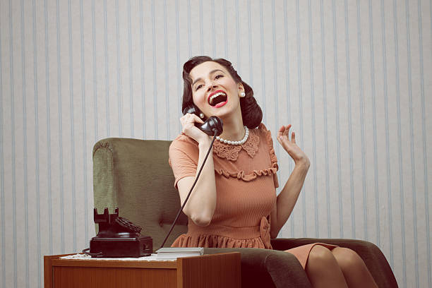 cheerful woman talking on landline phone - 1950s style stock photos and pictures