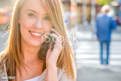 624206636 istock photo Cheerful woman talking on the phone in the street 589579342
