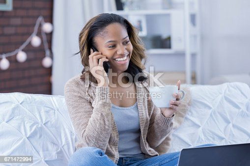 istock Cheerful woman talks on phone at home 671472994