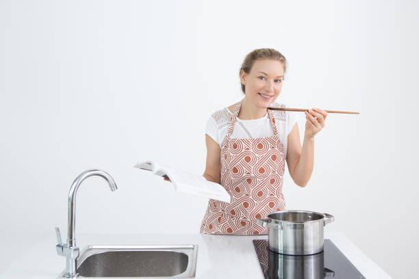 fröhliche frau, die verkostung der zubereiteten speisen - pfannen test stock-fotos und bilder