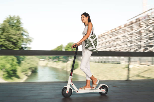 Cheerful woman tourist exploring the city on electric scooter stock photo