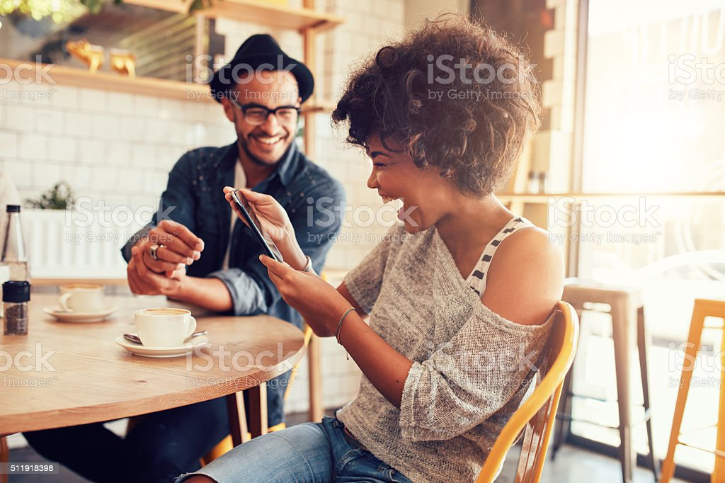 Portrait of smiling young woman at a cafe table looking at digital...
