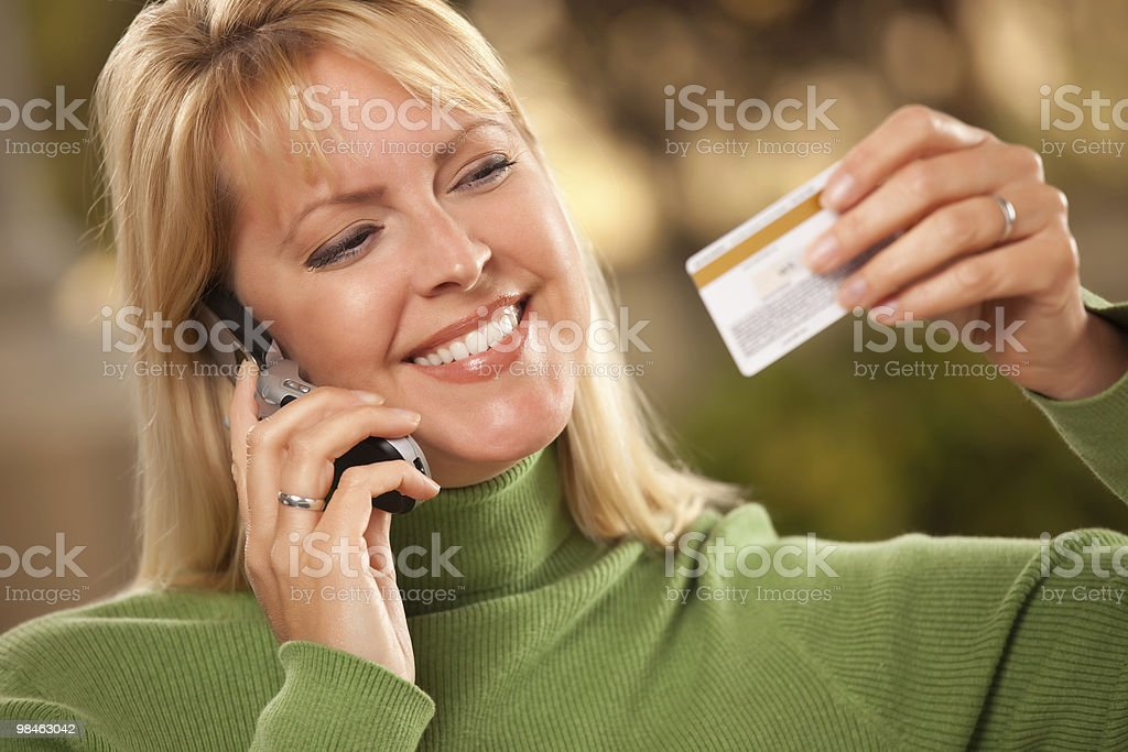 Cheerful Woman Using Her Phone with Credit Card royalty-free stock photo
