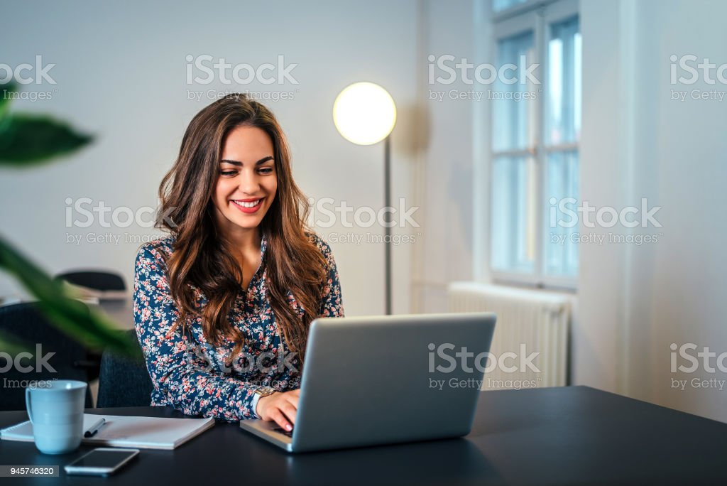 Cheerful woman using laptop at workplace. stock photo
