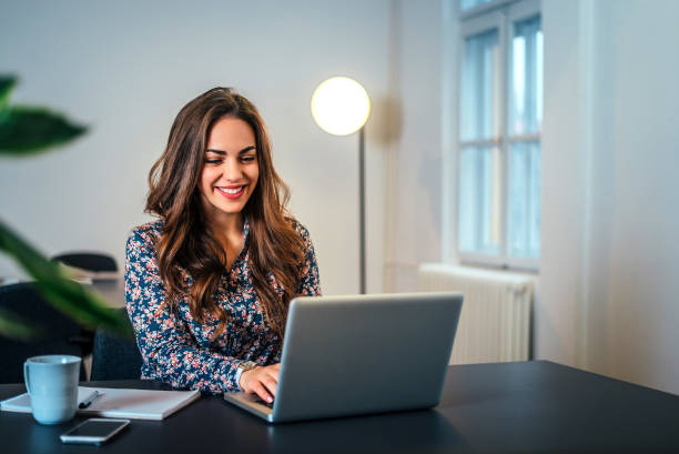 cheerful woman using laptop at workplace. - using laptop stock photos and pictures