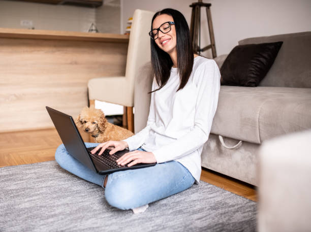 Cheerful  woman using laptop while sitting on floor at home.  Dog sitting next to her stock photo
