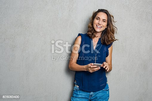 istock Cheerful woman using phone 825083400