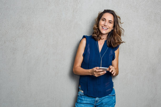 Cheerful woman using phone stock photo