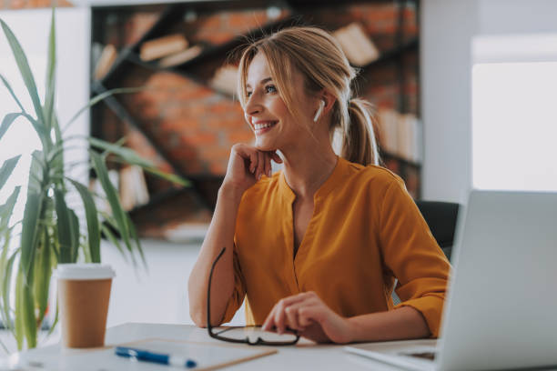 Cheerful woman wearing wireless earphones and smiling Listening to music. Happy young woman sitting in the office with laptop and coffee while using modern wireless earphones blouse stock pictures, royalty-free photos & images