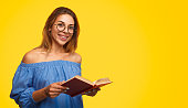 Pretty female in stylish glasses smiling and holding open book while standing on vivid yellow background