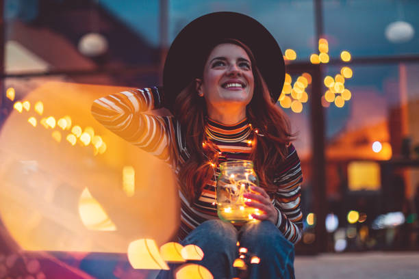 Cheerful woman with Christmas lights Cheerful woman with Christmas lights christmas fun stock pictures, royalty-free photos & images
