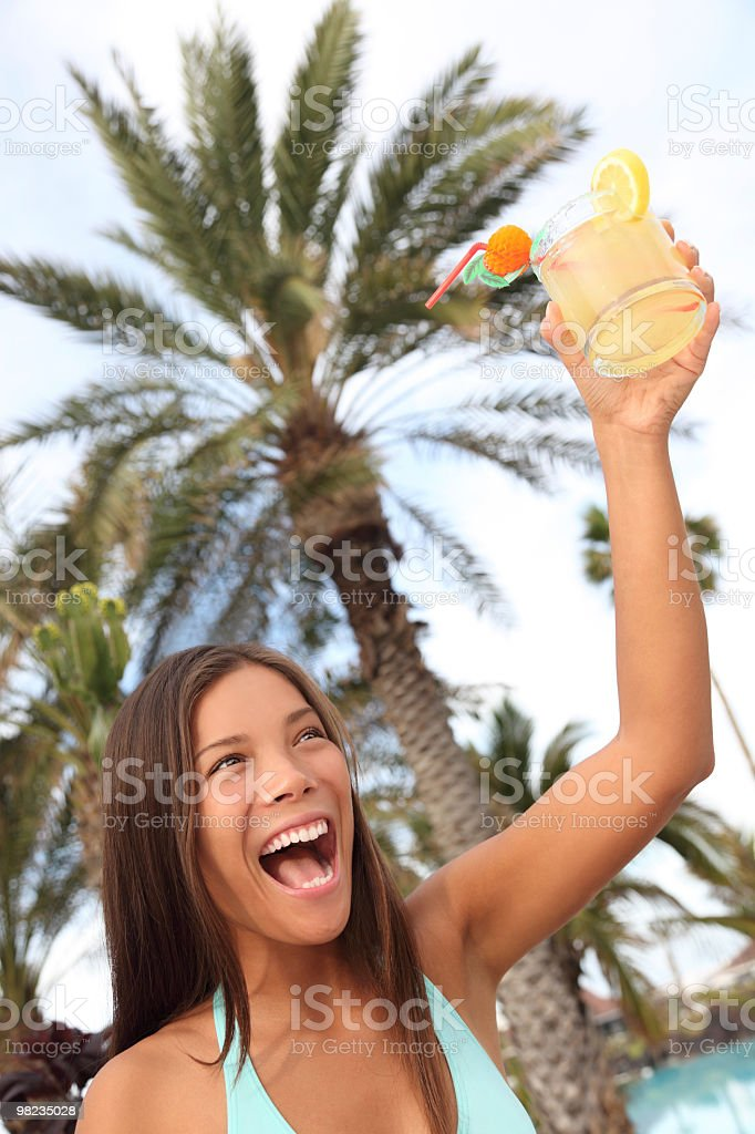 Cheerful woman with drink at tropical resort toasting royalty-free stock photo