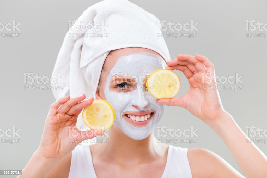 Cheerful woman with facial mask holding slices of lemon - foto de acervo