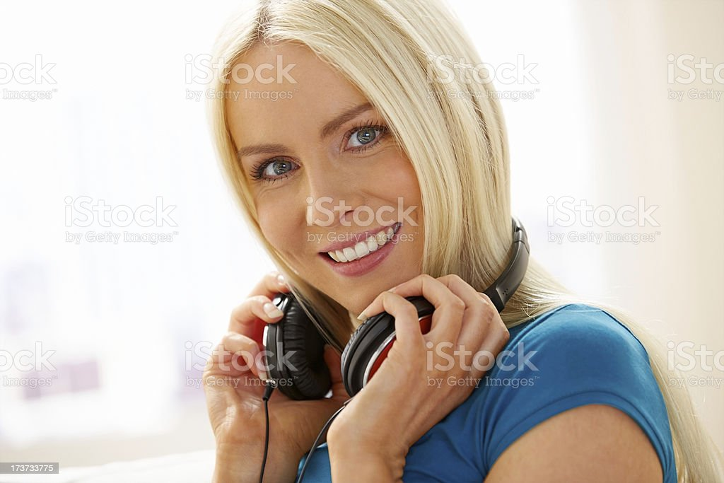 Cheerful woman with headphones listening to music at home royalty-free stock photo