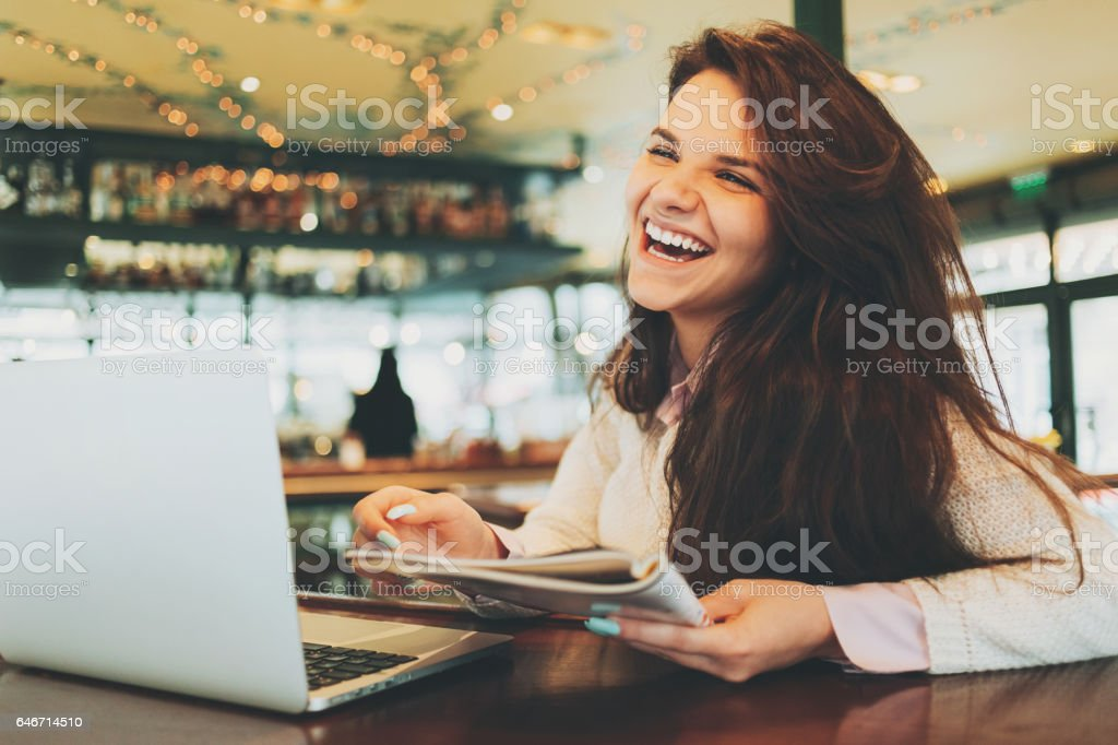 Cheerful woman with laptop and magazine in the bar stock photo