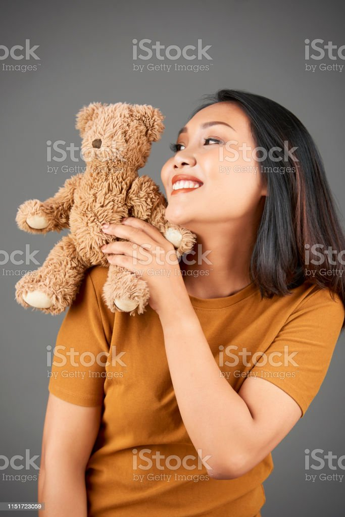 Pretty positive young Vietnamese woman with teddy bear sitting on her...