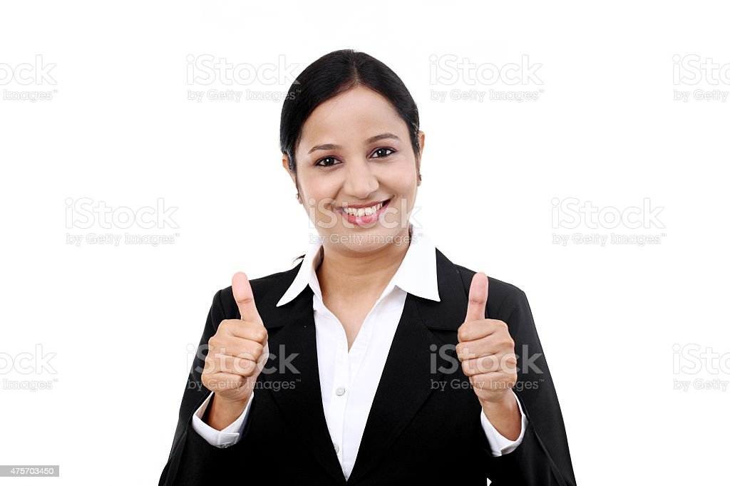 Cheerful woman with thumbs up against white background stock photo