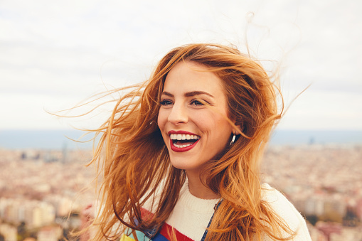 istock Cheerful woman with tousled hair against cityscape 695593416