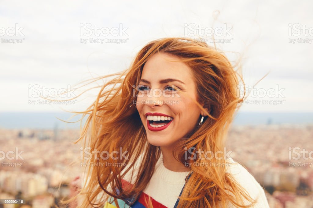 Cheerful woman with tousled hair against cityscape stock photo