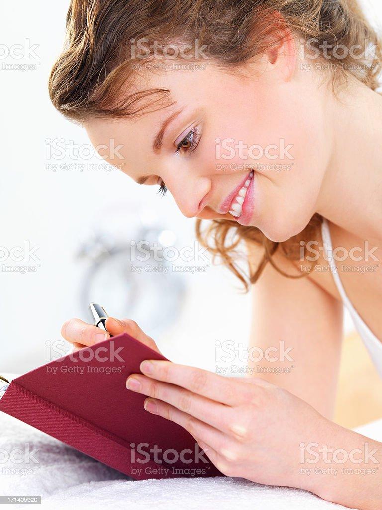 Cheerful woman writing diary royalty-free stock photo