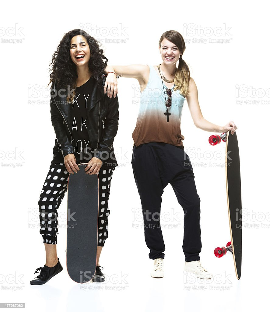 Cheerful women standing with skateboards royalty-free stock photo