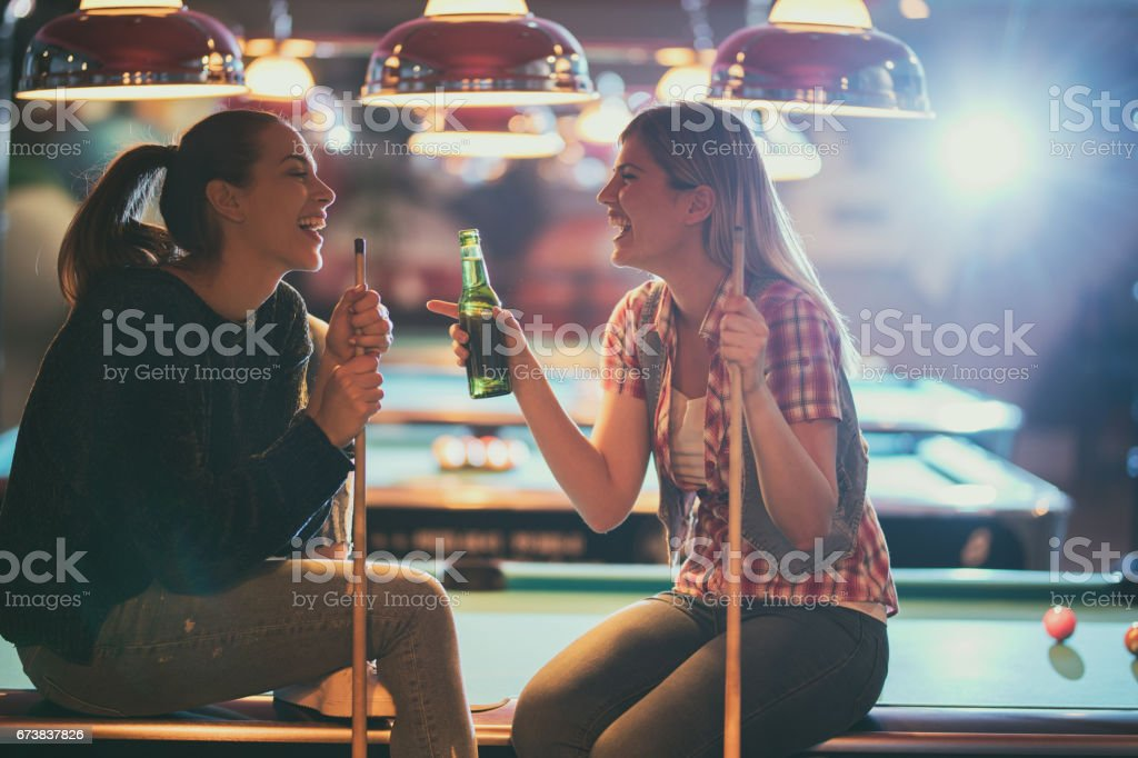 Cheerful women talking about something funny in a pool hall. stock photo