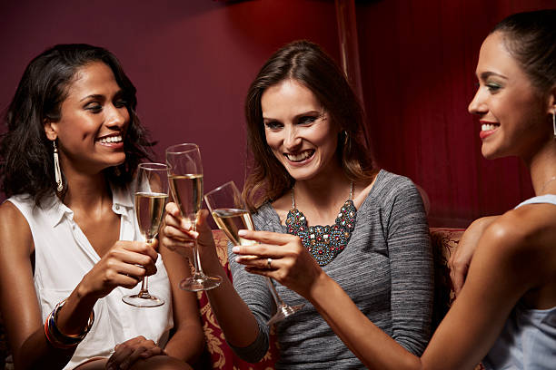 Cheerful women toasting champagne in nightclub stock photo