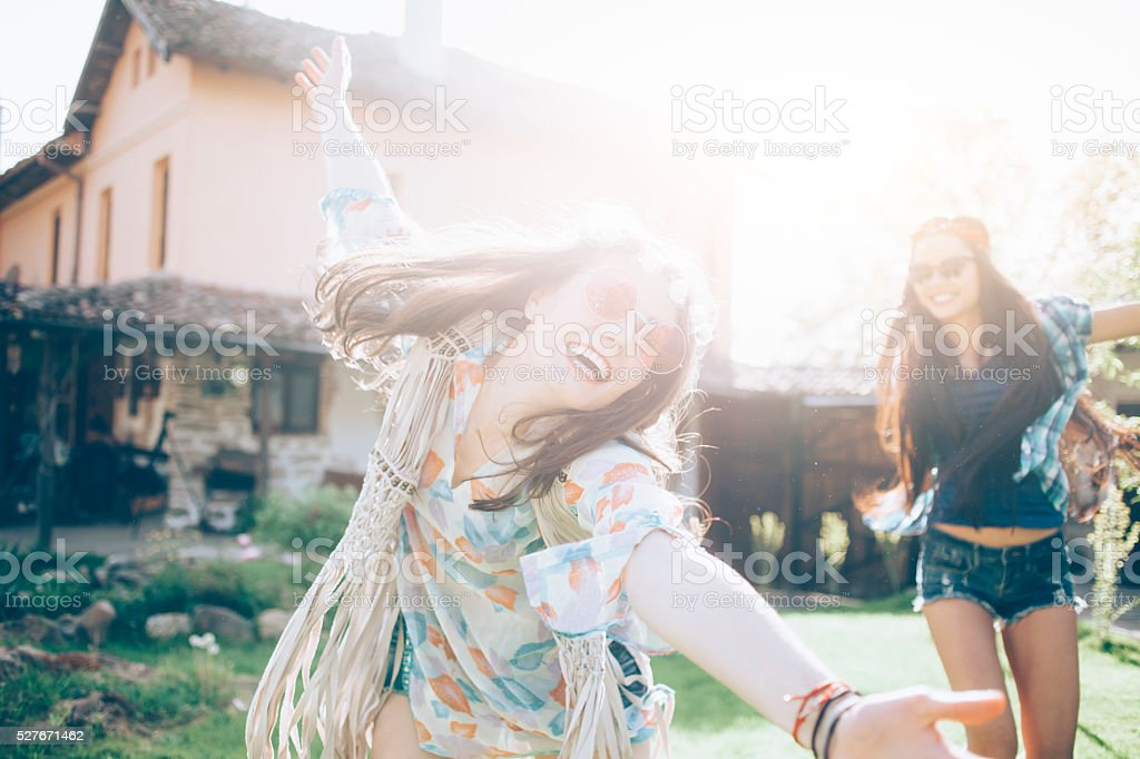 Cheerful women with daisies wreath dancing outdoor stock photo