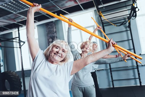 936573360 istock photo Cheerful women with stick doing side bending exercise at gym 936573428